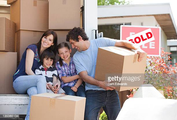 Family unloading boxes from moving van