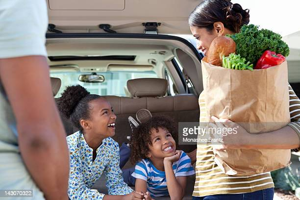 family unloading groceries from car - unloading stock pictures, royalty-free photos & images