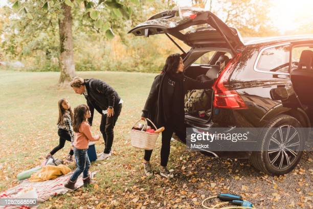 family unloading luggage from electric car on field during picnic - 積荷を降ろす ストックフォトと画像