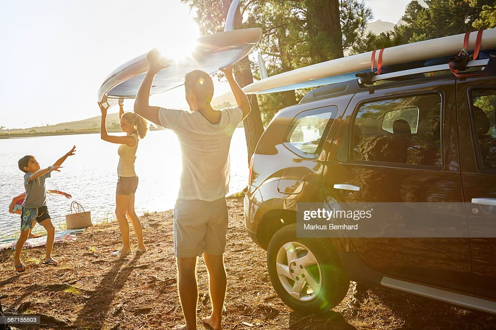 Family unloading stand-up paddle board. : Stock Photo