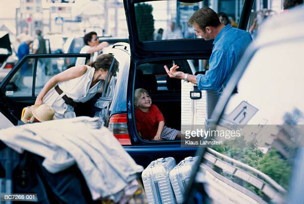 Family unloading suitcases from car