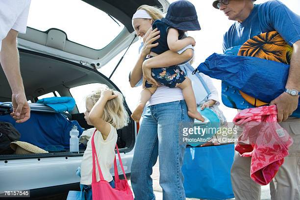 Family unloading trunk of car