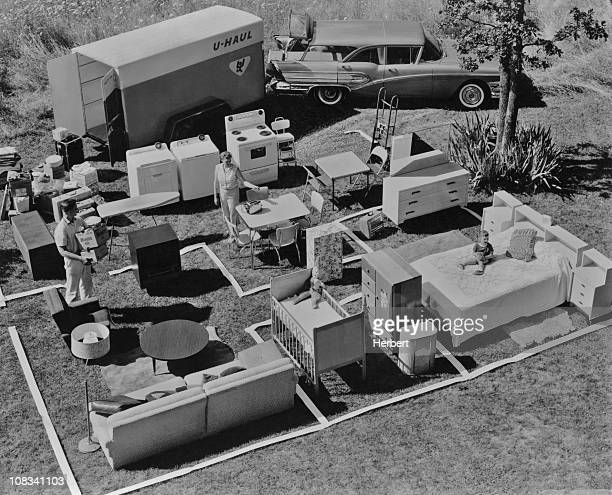 A family unpack their furniture from a UHaul trailer and arrange it on a floor plan marked out on the grass USA circa 1955