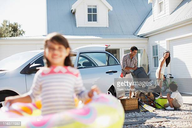 Family unpacking car in driveway