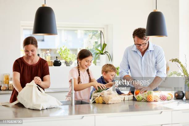 family unpacking groceries at kitchen island - danish food stock pictures, royalty-free photos & images