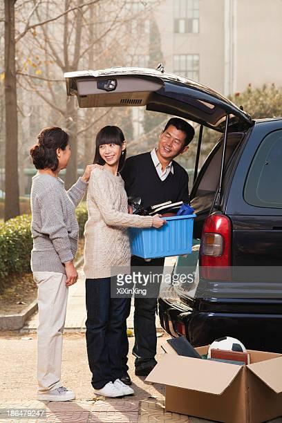 Family unpacking minivan for college, Beijing