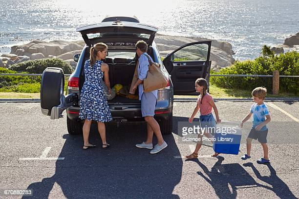 Family unpacking the car by the beach