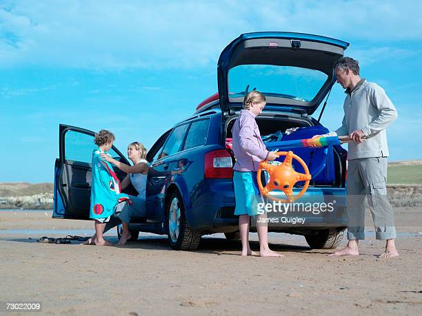 Family unpacking toys from car on beach