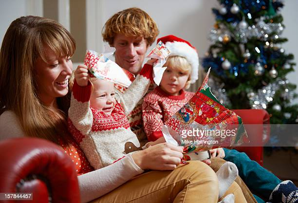 Family unwrapping Christmas presents on sofa.