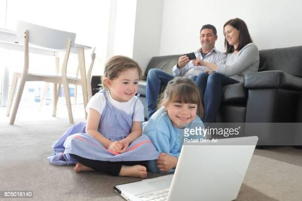 family use wireless devices at home - rafael ben ari fotografías e imágenes de stock