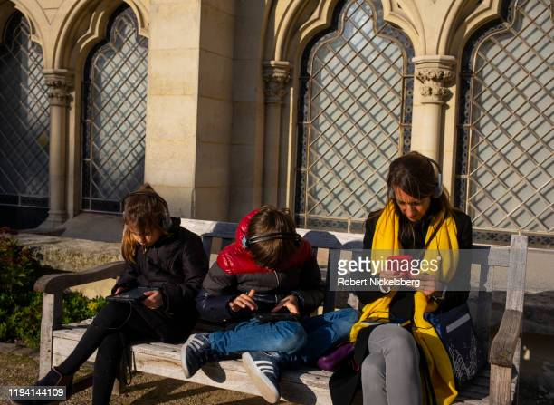 Family uses electronic audio devices as a museum guide while sitting in a garden at the Musée Rodin in Paris, France, November 9, 2019. The museum...