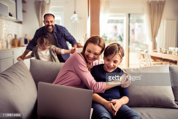 family using a laptop - teasing stock pictures, royalty-free photos & images