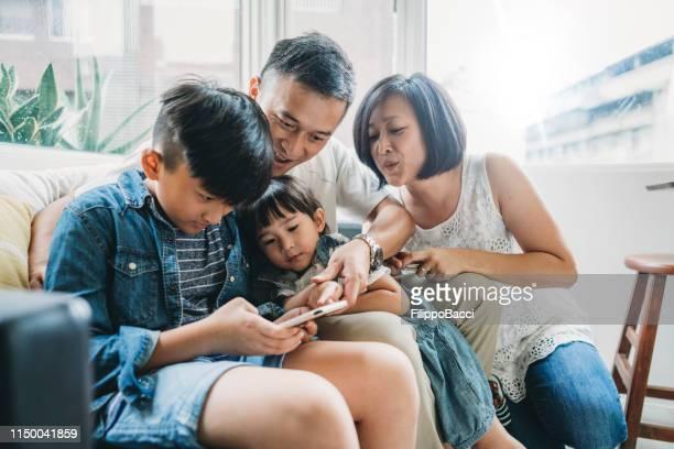 自宅でソファに座って一緒に携帯電話を使用して家族 - 東洋文化 ストックフォトと画像