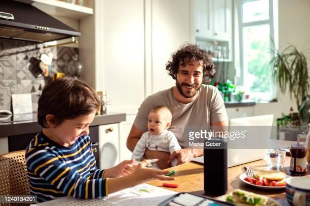 family using a smart speaker - cuisine non professionnelle photos et images de collection