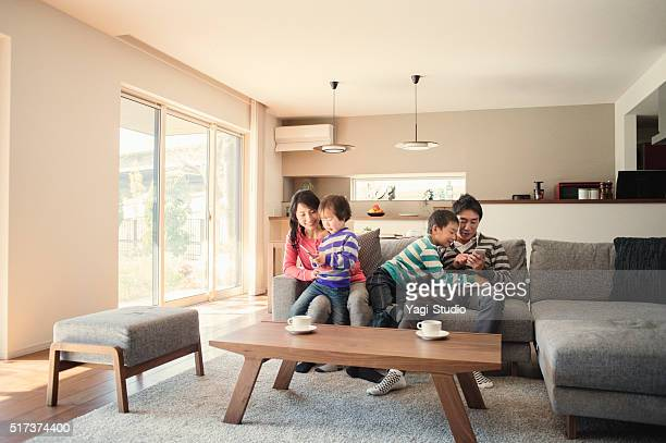 family using digital tablet and smart phone together at home. - japan mom and son stock photos and pictures