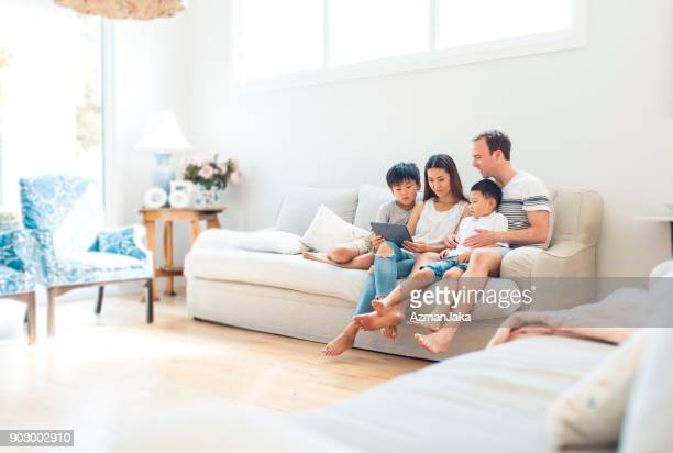 family using digital tablet in living room - mixed race person stock pictures, royalty-free photos & images