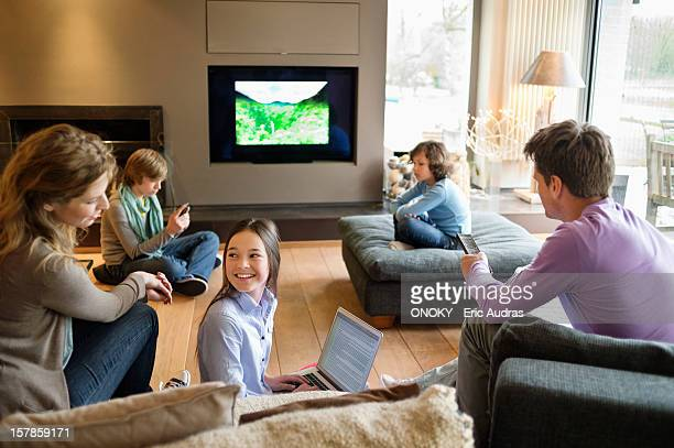 Family using electronic gadgets in a living room
