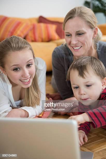 Family using laptop in living room, smiling