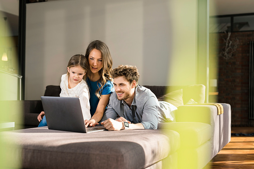 Family using laptop on sofa at home - gettyimageskorea