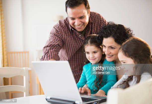 Family using laptop together at table