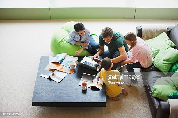 family using laptop together in living room - mixed magazine stock photos and pictures