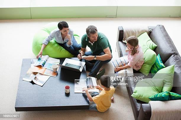 Famille à l'aide d'ordinateur portable ensemble dans la salle de séjour