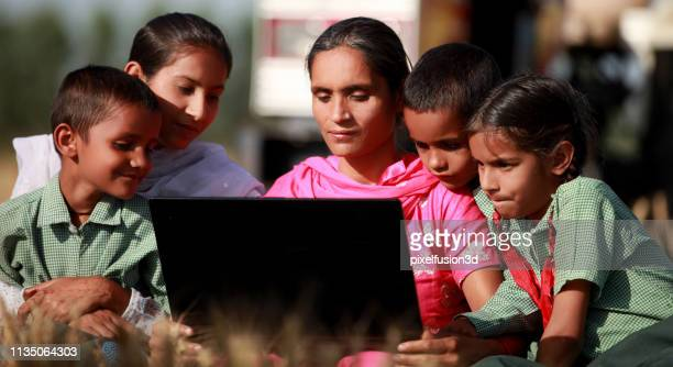 family using laptop together outdoor in nature - salwar kameez stock pictures, royalty-free photos & images
