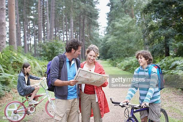 familie mit karte im wald - erforschung stock-fotos und bilder