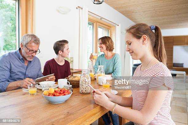 Family using portable devices during breakfast at home