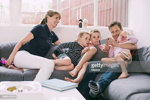 Family using smart phone on sofa at home