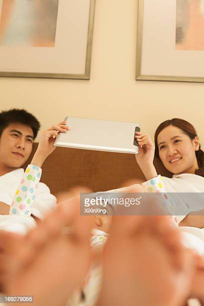 Family Using Tablet in Bed