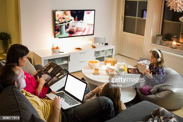 family using technologies in living room - arts culture and entertainment stock pictures, royalty-free photos & images