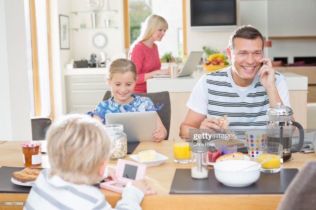 Family using technology at breakfast : Stock Photo