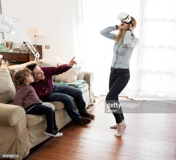 family using virtual reality goggles at home - 3d mom son stock photos and pictures