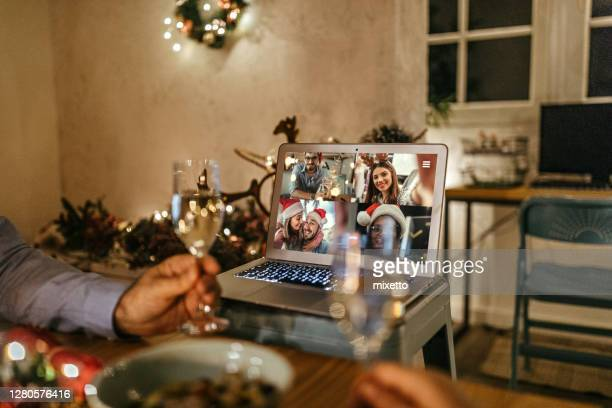family video chatting online on the occasion of christmas celebration - party social event stock pictures, royalty-free photos & images