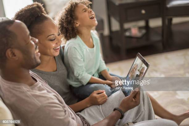 family video chatting with digital tablet - mid adult stock pictures, royalty-free photos & images