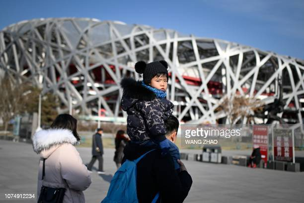 A family visit the National Stadium also known as the Bird's Nest national stadium constructed for the 2008 Olympic Games in Beijing on December 26...