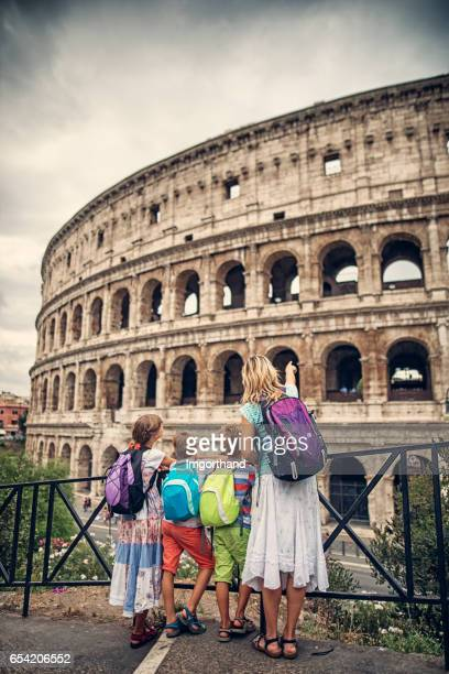 family visiting colloseum in rome, italy - coliseum rome stock photos and pictures