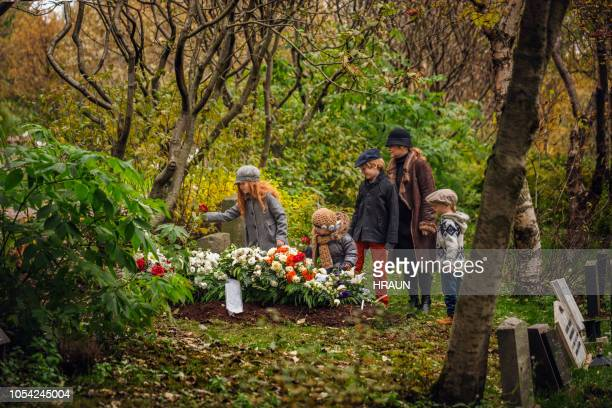 family visiting grave of deceased loved one. - funeral stock pictures, royalty-free photos & images
