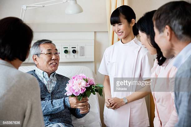 Family visiting happy senior man holding flowers in ward