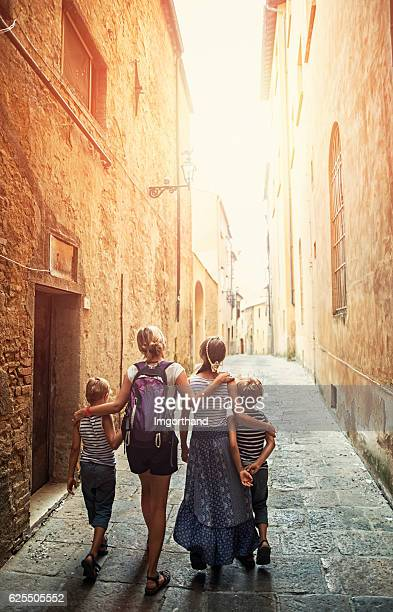 family visiting italian town of volterra, tuscany - volterra stock photos and pictures