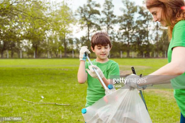 family volunteering for cleanup in park - izusek stock pictures, royalty-free photos & images