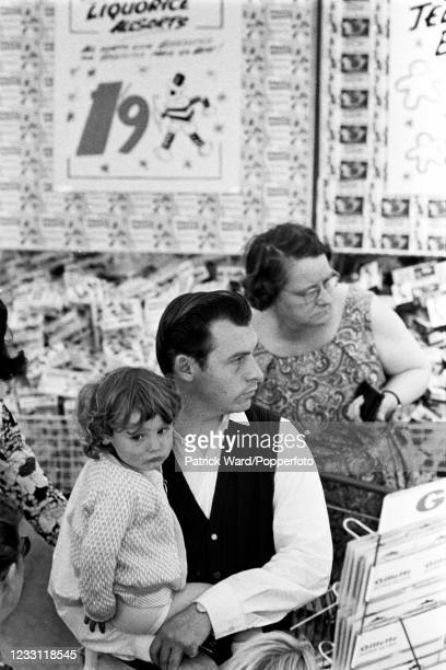 Family waiting in a supermarket queue in West London, circa July 1969. From a series of images to illustrate the many frustrations of living in...