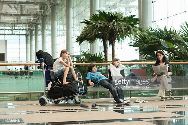 family waiting in airport terminal - wachten stockfoto's en -beelden
