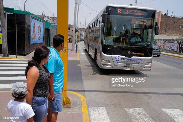 Family waiting to cross the road as the Metropolitano bus passes