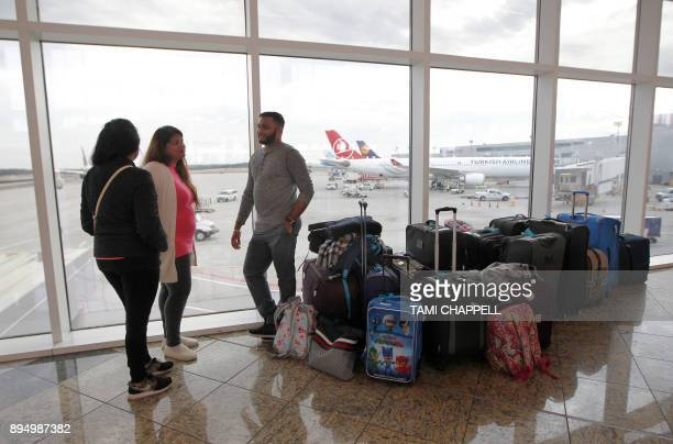 A family waits for their flight at the International terminal the day following a power outage caused by a fire at HartsfieldJackson Atlanta...
