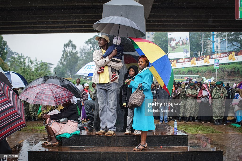 A family waits outside the University of Nairobi grounds despite the rain on November 26, 2015, to attend a mass delivered by Pope Francis in Nairobi, Kenya. Pope Francis makes his first visit to Kenya on a five day African tour that is scheduled to include Uganda and the Central African Republic. Africa is recognised as being crucial to the future of the Catholic Church with the continents Catholic numbers growing faster than anywhere else in the world.