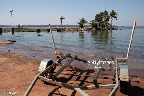A family walk across a pontoon to an abandoned floating restaurant on Lake Chivero on August 5 2018 in Harare Zimbabwe Lake Chivero is 32km South...