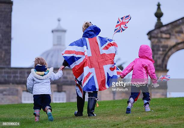A family walk across the lawn during the annual classical Proms Spectacular concert held on the north lawn of Castle Howard on August 20 2016 in York...