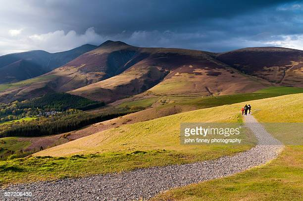 family walk along latrigg path with skiddaw mountain above. lake district national park. uk. europe. - keswick stock pictures, royalty-free photos & images